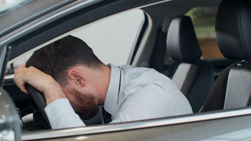 Le jeune homme s'asseyant ? l'int?rieur de la voiture est tr?s boulevers? et soumis ? une contrainte image stock