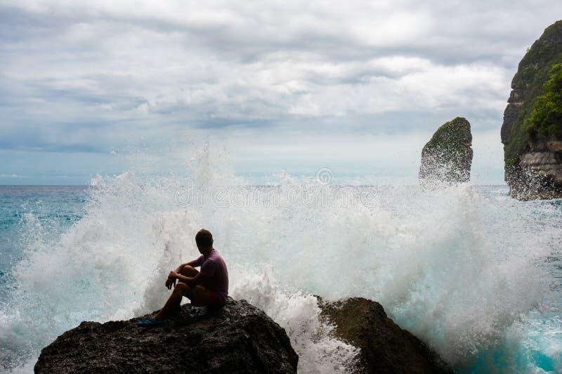 Le jeune homme s'asseyant sur la roche avec la mer ondule le rodage l'avant photo stock