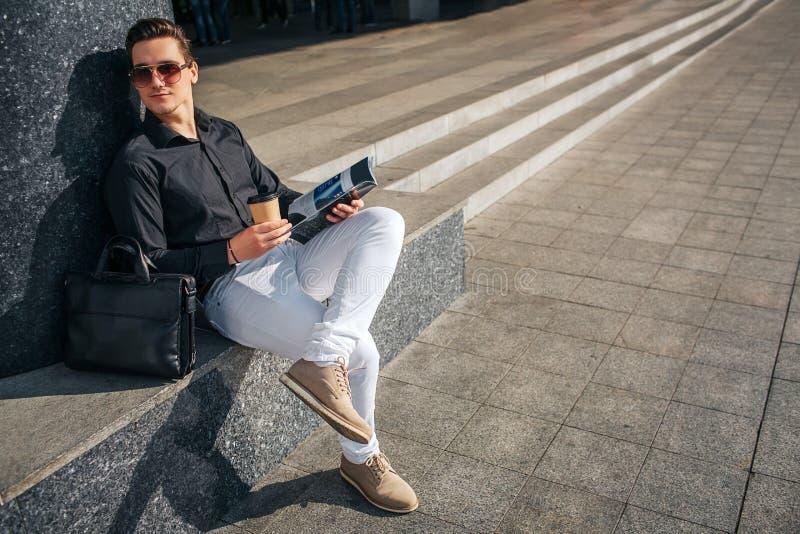 Le jeune homme s'asseyent sur des étapes et le regard par des verres pour redresser Il tient la tasse du café et du journal Le ty photographie stock libre de droits