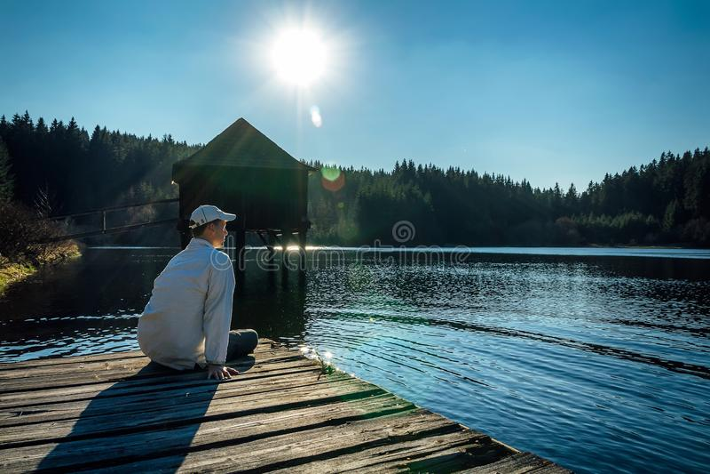 Le jeune homme s'asseyent sur le petit quai en bois sur l'étang avec le bâtiment en bois et le ciel bleu images libres de droits