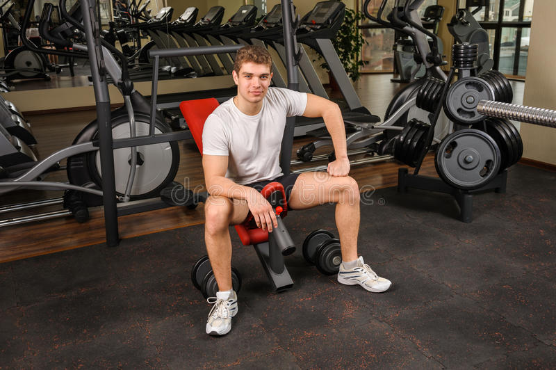 Le jeune homme s'assied après séance d'entraînement dans le gymnase images stock