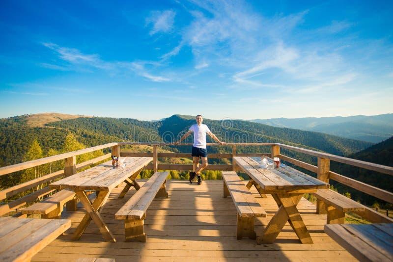 Le jeune homme s'assied en café d'air ouvert avec la terrasse et apprécie la belle vue des montagnes photo stock