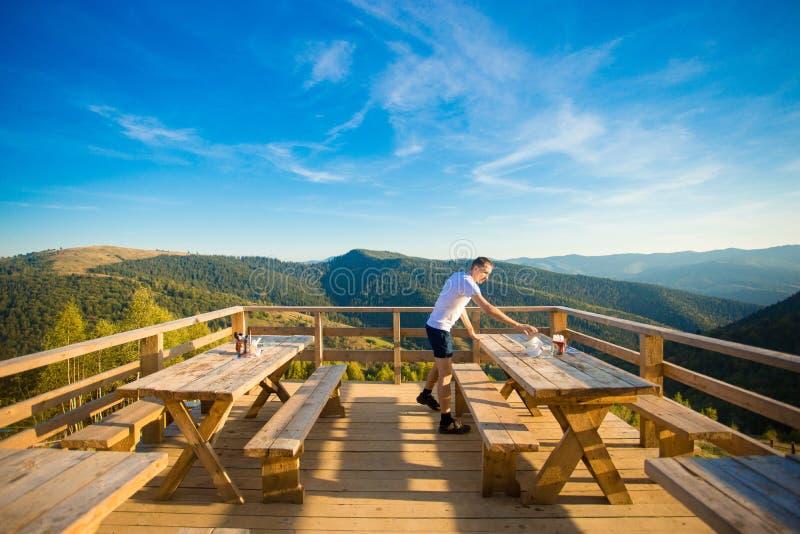 Le jeune homme s'assied en café d'air ouvert avec la terrasse et apprécie la belle vue des montagnes images libres de droits