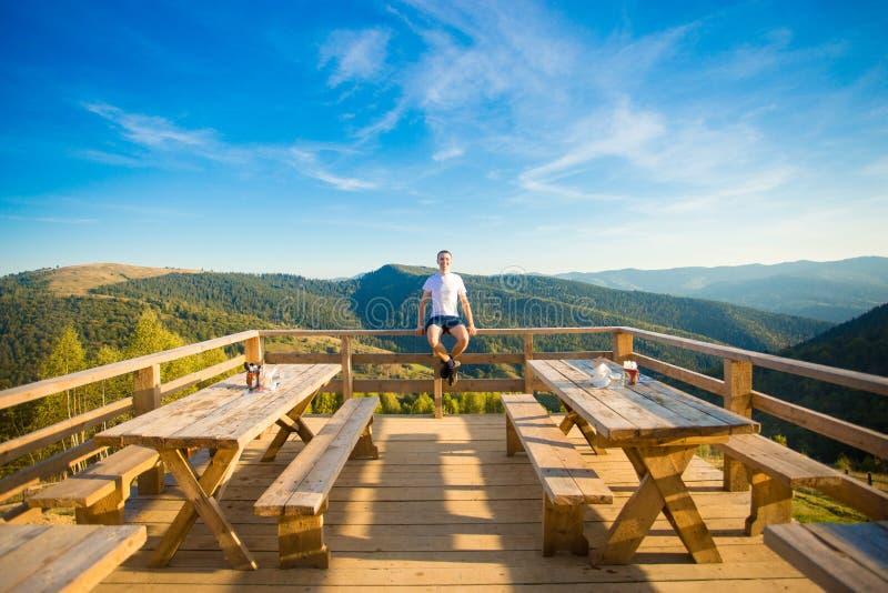 Le jeune homme s'assied en café d'air ouvert avec la terrasse et apprécie la belle vue des montagnes image libre de droits