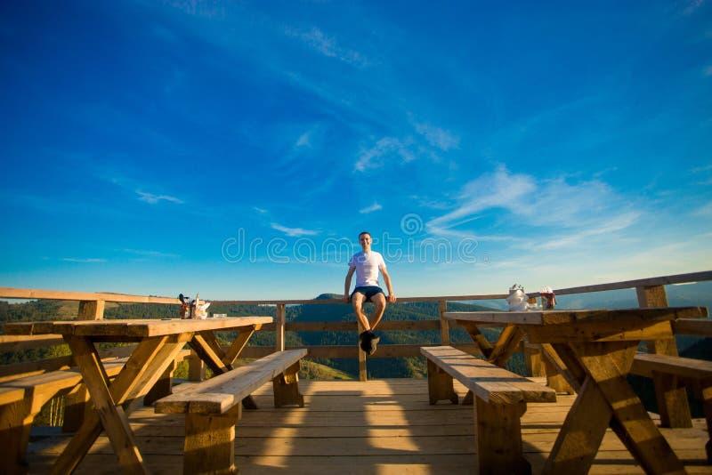 Le jeune homme s'assied en café d'air ouvert avec la terrasse et apprécie la belle vue des montagnes photos libres de droits