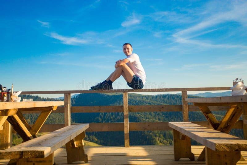 Le jeune homme s'assied en café d'air ouvert avec la terrasse et apprécie la belle vue des montagnes photo libre de droits