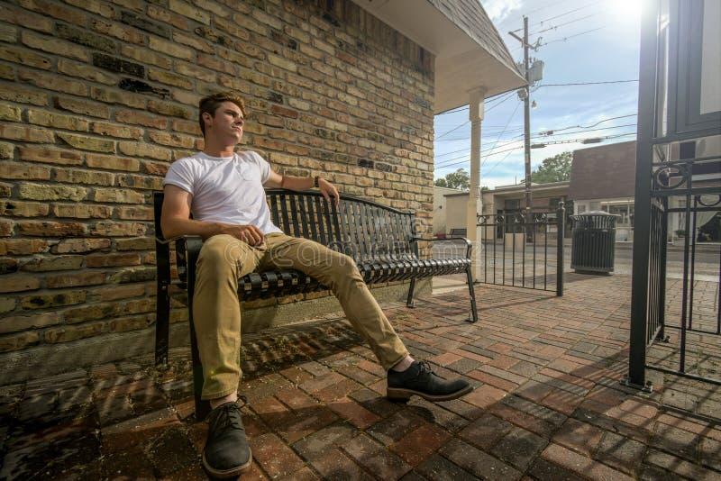 Le jeune homme s'assied sur le banc d'extérieur image libre de droits