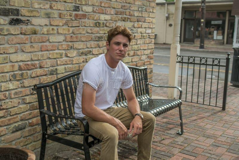 Le jeune homme s'assied sur le banc d'extérieur image stock