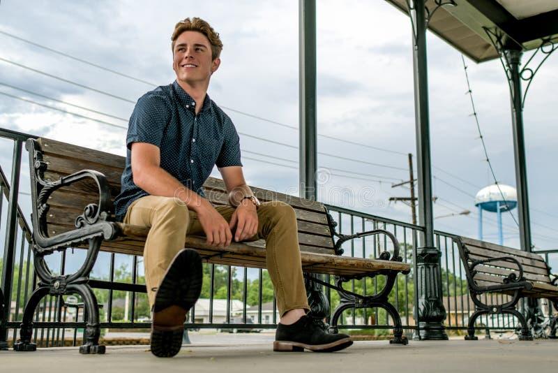 Le jeune homme s'assied sur le banc de station de train photo stock