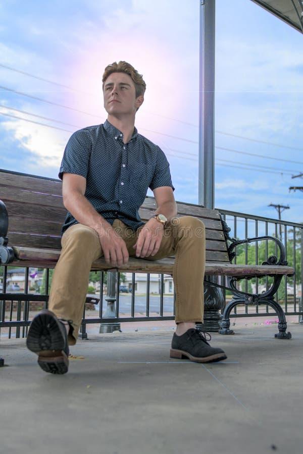 Le jeune homme s'assied sur le banc de station de train photo libre de droits