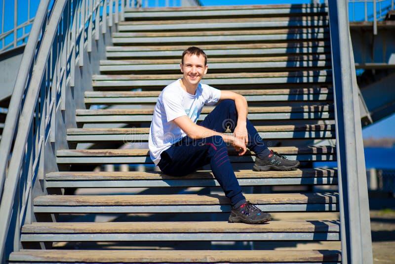 Le jeune homme s'assied sur des escaliers dans le jour ensoleillé photo stock