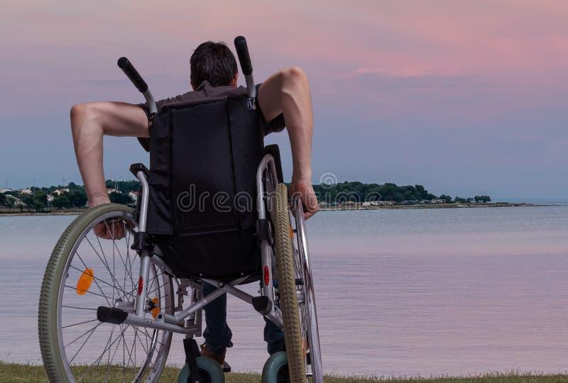 Le jeune homme s'assied sur le fauteuil roulant près de la mer au coucher du soleil image stock