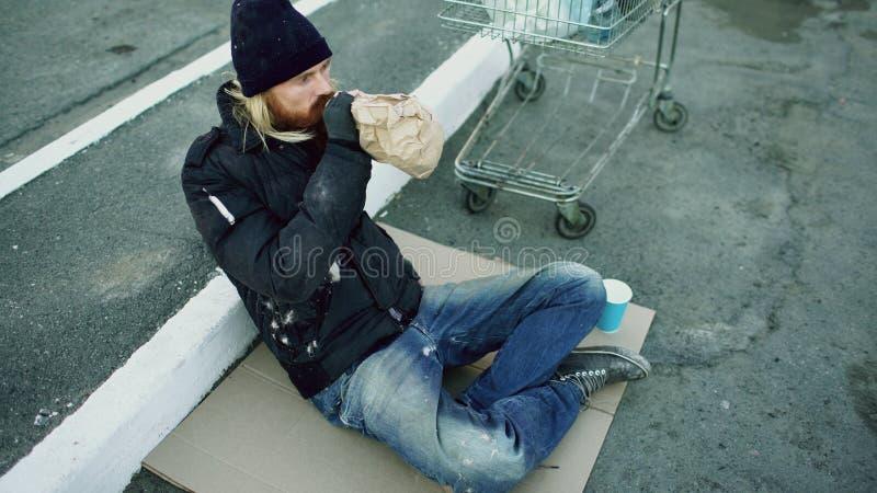 Le jeune homme sans abri dans des vêtements sales boivent l'alcool se reposant près du caddie sur la rue au jour d'hiver froid photographie stock
