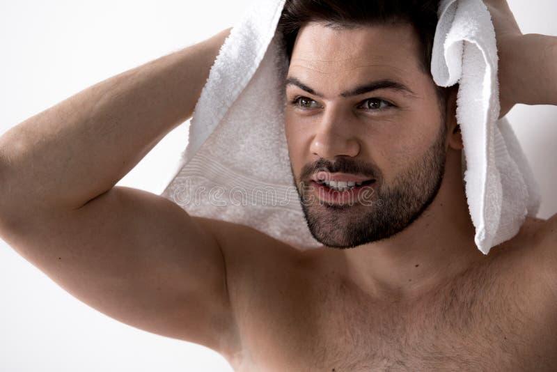 Le jeune homme sans chemise joyeux essuie sa tête photo stock