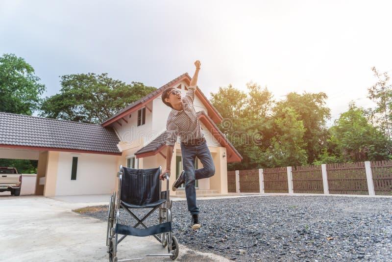 Le jeune homme sautant étroitement du fauteuil roulant et récupéré de la paralysie images libres de droits