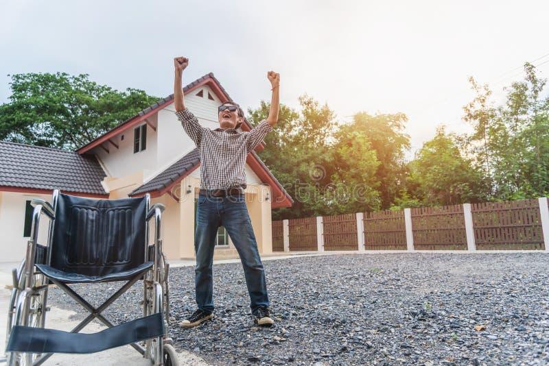 Le jeune homme sautant étroitement du fauteuil roulant et récupéré de la paralysie images stock