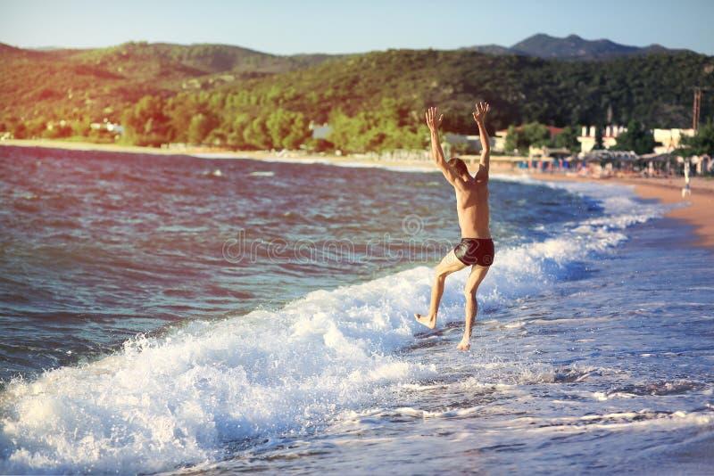 Le jeune homme sautant dans la mer au coucher du soleil photographie stock
