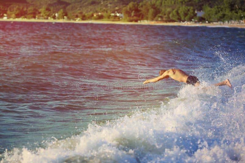 Le jeune homme sautant dans la mer au coucher du soleil photos libres de droits