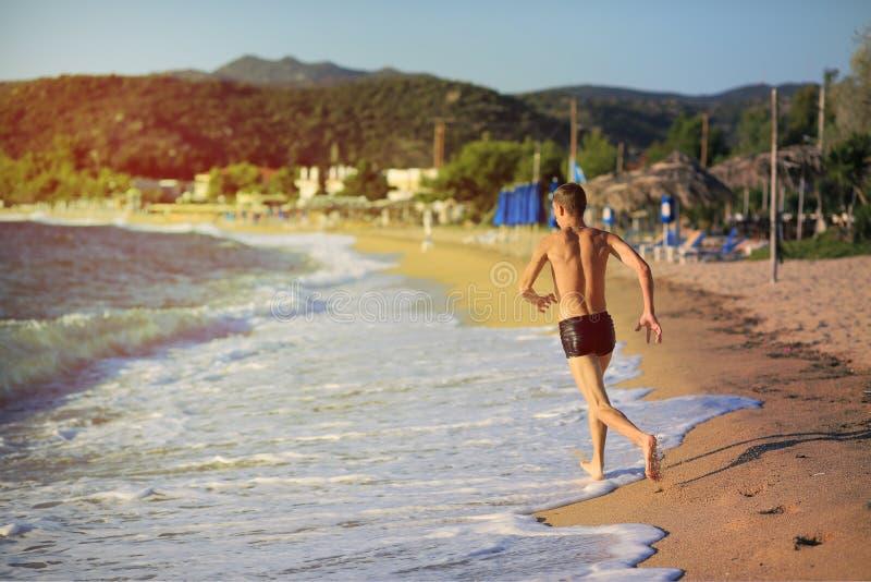 Le jeune homme sautant dans la mer au coucher du soleil photos stock