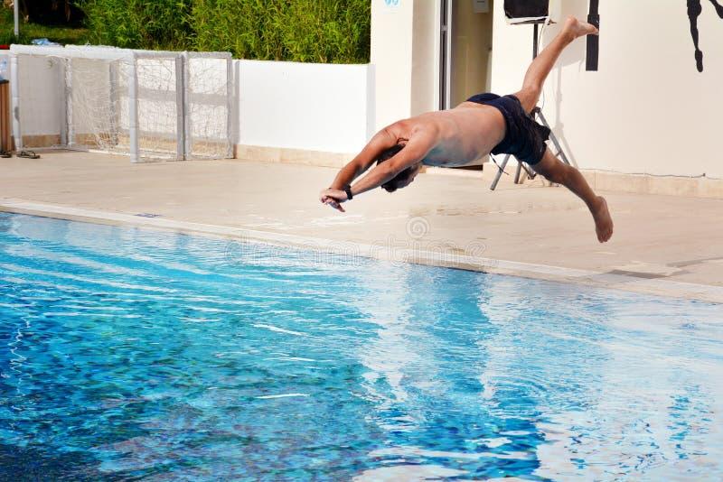 Le jeune homme sautant dans la piscine photographie stock libre de droits