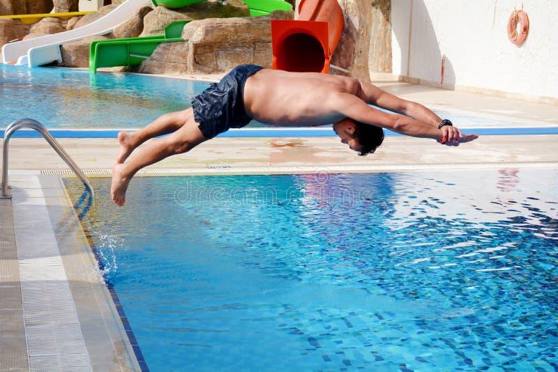 Le jeune homme sautant dans la piscine image stock