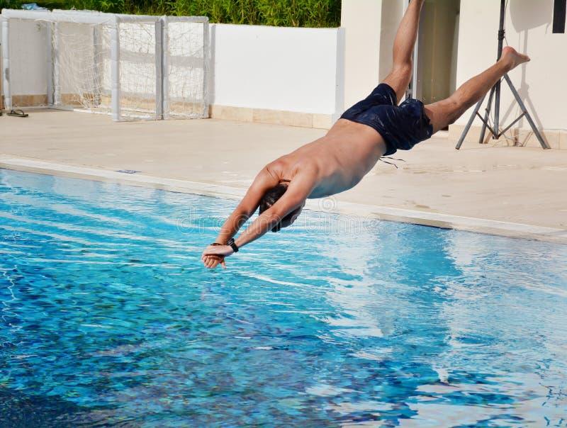 Le jeune homme sautant dans la piscine photos stock