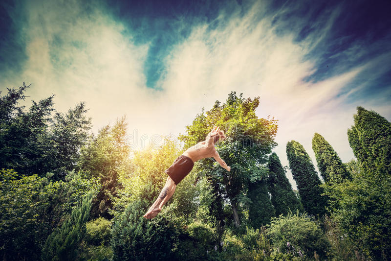 Le jeune homme sautant haut dans un jardin images stock
