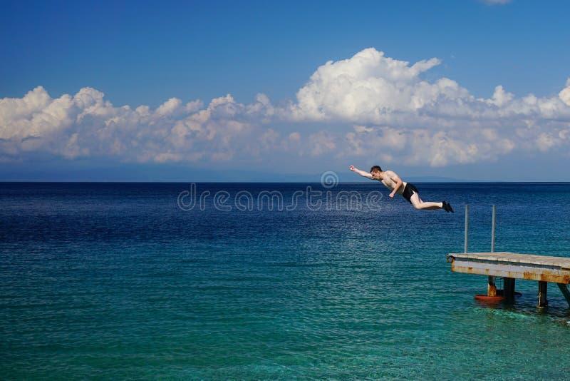 Le jeune homme sautant outre du pilier dans l'eau photo stock