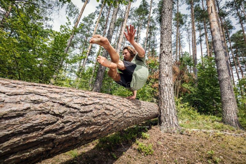 Le jeune homme sautant par-dessus un tronc d'arbre dans la forêt photographie stock