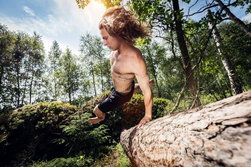 Le jeune homme sautant par-dessus un tronc d'arbre dans la forêt images libres de droits