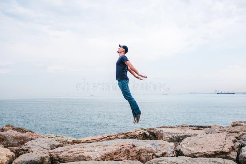 Le jeune homme sautant vers le haut dépeignant un vol dans la perspective de la mer et du ciel le concept de la liberté durée image stock