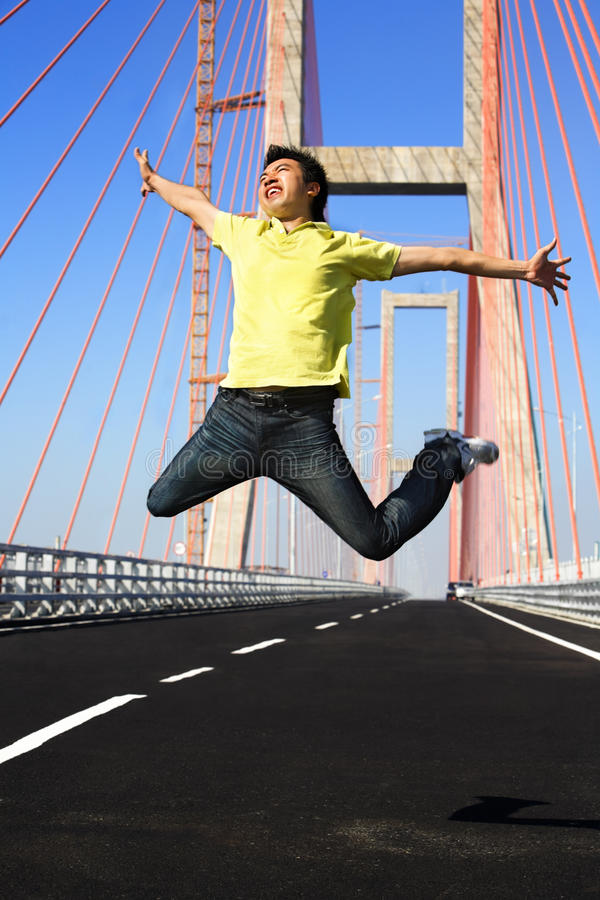 Le jeune homme sautent très haut dans la zone de passerelle image libre de droits