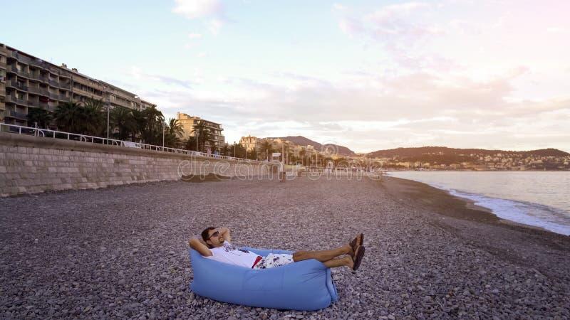 Le jeune homme se couchant sur le sofa de repaire pour apprécier le repos sur la plage de mer, été détendent photos libres de droits