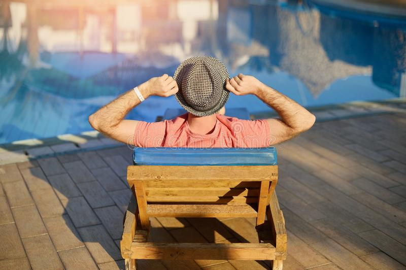 Le jeune homme se reposant sur des canapés de Sun par la natation détendent en été de piscine sur un canapé du soleil à l'hôtel s photo libre de droits