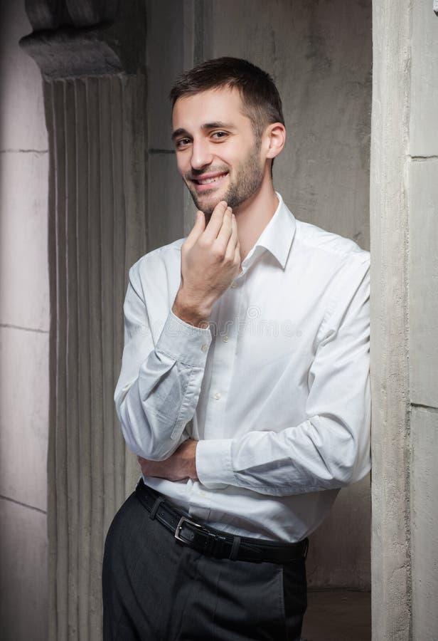 Le jeune homme se tient à un mur photographie stock libre de droits