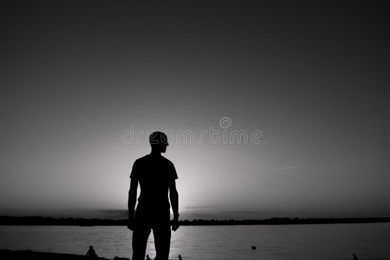 Le jeune homme se tient devant la berge avec le lever de soleil ou le coucher du soleil arrière et blanc image stock
