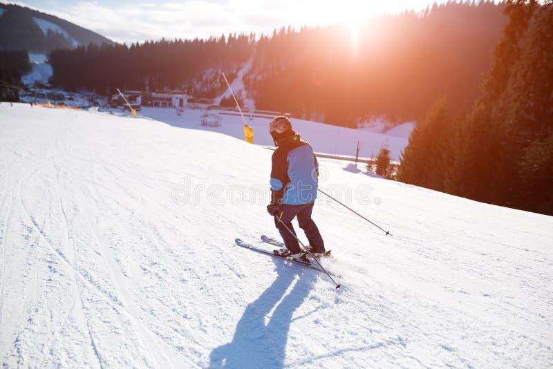 Le jeune homme skie à une station de sports d'hiver dans les montagnes photos libres de droits