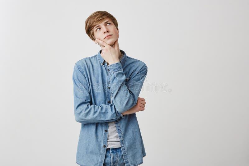 Le jeune homme songeur avec les cheveux et les yeux bleus justes, a l'expression du visage sérieuse, recherche, garde des doigts  photo libre de droits