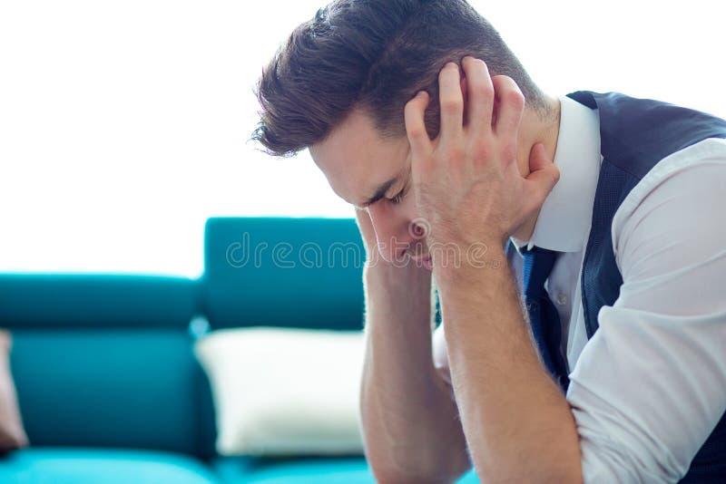Le jeune homme soumis à une contrainte d'affaires avec des mains sur le sentiment principal s'est inquiété photos libres de droits