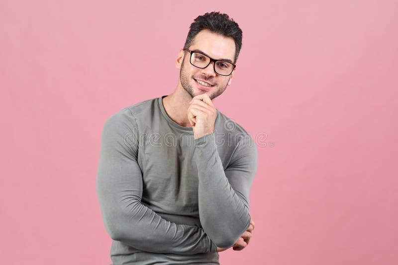 Le jeune homme sportif avec des verres avec un sourire positif regarde pensivement l'appareil-photo et sourit photos stock