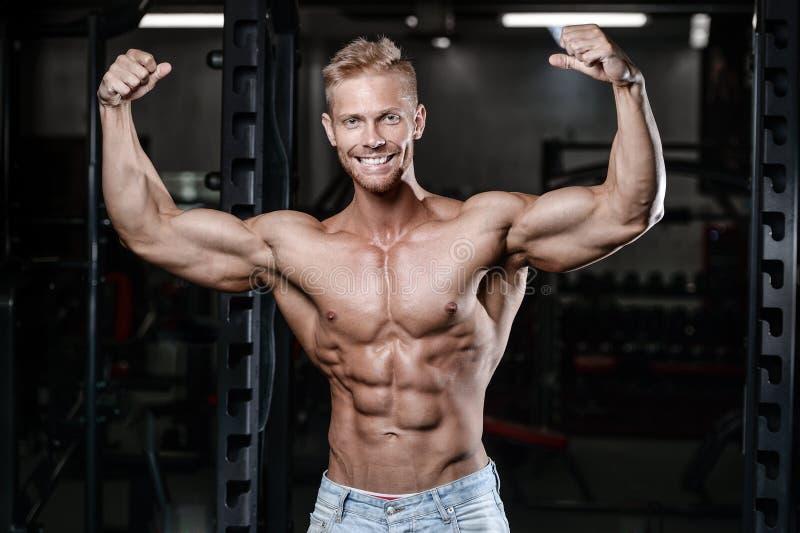 Le jeune homme sportif fort et beau muscles l'ABS et la forme physique et le bodybuilding de biceps photos libres de droits