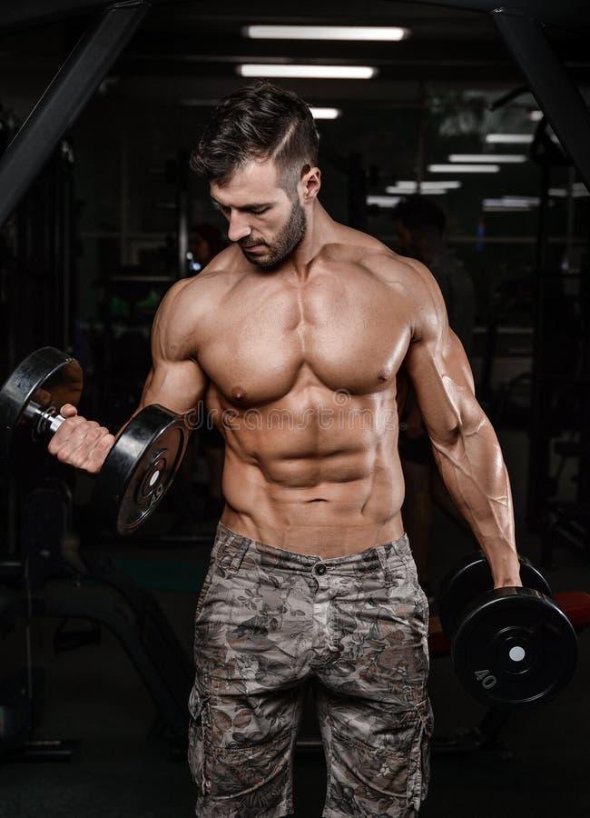 Le jeune homme sportif fort et beau muscles l'ABS et le biceps photographie stock libre de droits