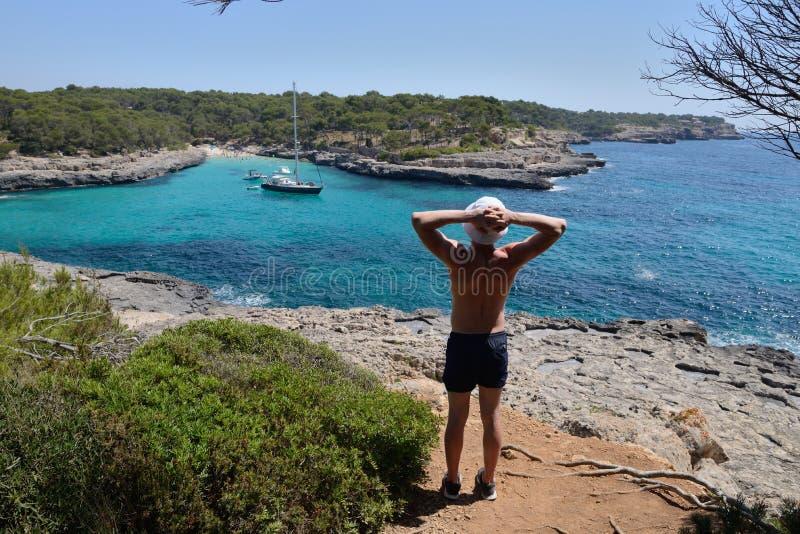 Le jeune homme sur une roche contemple un paysage marin photographie stock