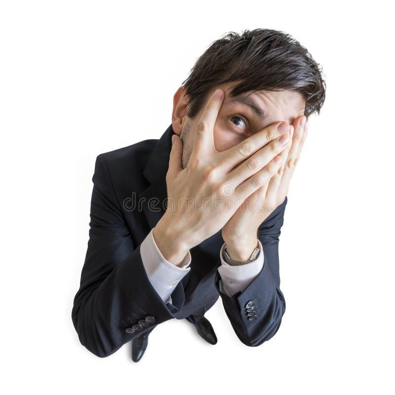 Le jeune homme timide couvre son visage de mains et regarde par des doigts Vue de ci-avant D'isolement sur le fond blanc photo libre de droits