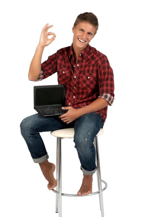 Le jeune homme travaille sur l'ordinateur portatif. image libre de droits