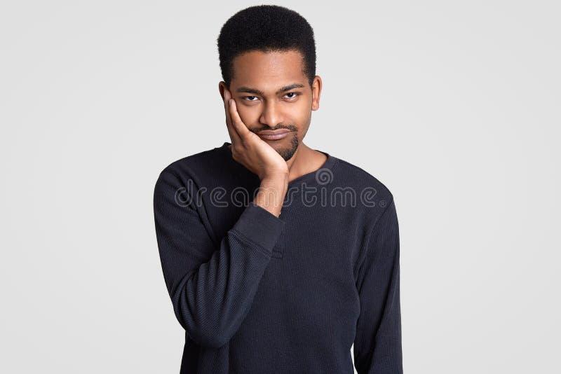 Le jeune homme triste noir regarde avec l'expression avec affliction, tient le menton, a la coupe de cheveux courte, peau foncée, photographie stock libre de droits