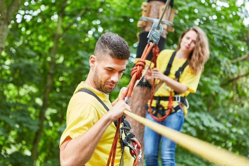 Le jeune homme va roped au-dessus d'un pont photographie stock libre de droits
