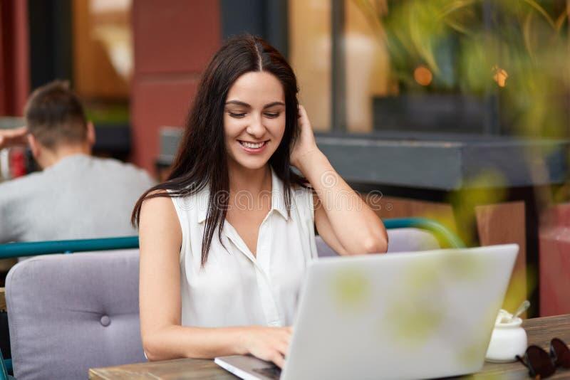 Le jeune indépendant féminin gai travaille sur l'ordinateur portable dans les Bistros, a le sourire toothy comme les finitions fo photos libres de droits