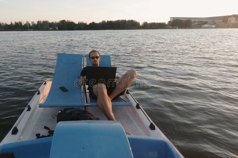 Le jeune indépendant travaille sur l'ordinateur sur un bateau Affaires à distance revenus passifs photos libres de droits