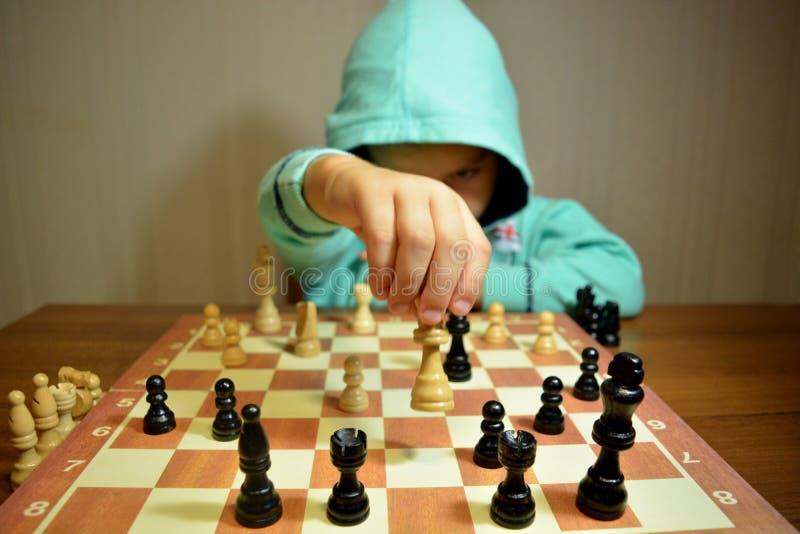 Le jeune joueur d'échecs joue aux échecs images stock